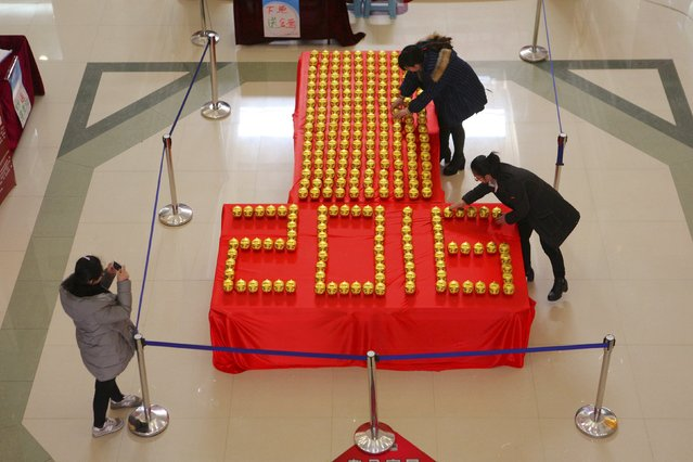 """Workers arrange piggy banks to form the year """"2016"""" ahead of the new year at a shopping mall in Binzhou, Shandong province, China, December 31, 2015. (Photo by Reuters/Stringer)"""
