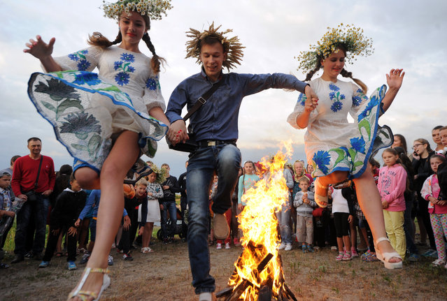 Young people jump over a bonfire as they take part in the Ivan Kupala Night celebration, a traditional Slavic holiday, outside the small town of Turov, some 270 km south of Minsk, on July 6, 2016. People celebrate Kupala Night with bonfires that last throughout the night with some leaping over the flames as it is believed that the act of jumping over the bonfire cleanses people of illness and bad luck. (Photo by Sergei Gapon/AFP Photo)