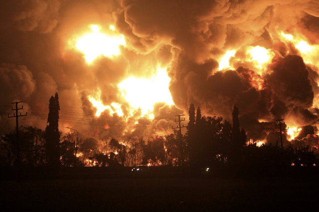 Cars pass by as fire razes through Pertamina Balongan Refinery in Indramayu, West Java, Indonesia, early Monday, March 29, 2021. Hundreds of people were evacuated from a nearby village after the massive fire broke out at the refinery. (Photo by AP Photo/Stringer)