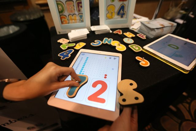 Smart Letters interactive wooden letters are used with a Marbotic app on a tablet for learning skills at The CES Unveiled press event, January 4, 2016 in Las Vegas, Nevada ahead of the CES 2016 Consumer Electronics Show. (Photo by David McNew/AFP Photo)
