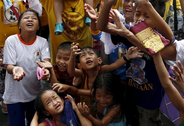 Children and other devotees wait to be sprinkled with holy water two days before the annual procession of the Black Nazarene in Manila January 7, 2016. (Photo by Erik De Castro/Reuters)