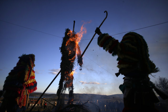 Revelers from the Portuguese village of Podence dressed in traditional costumes run and jump around a burning effigy of a traditional figure during annual Carnival festivities, in Podence, northeastern Portugal, Tuesday, February 17, 2015. (Photo by Francisco Seco/AP Photo)