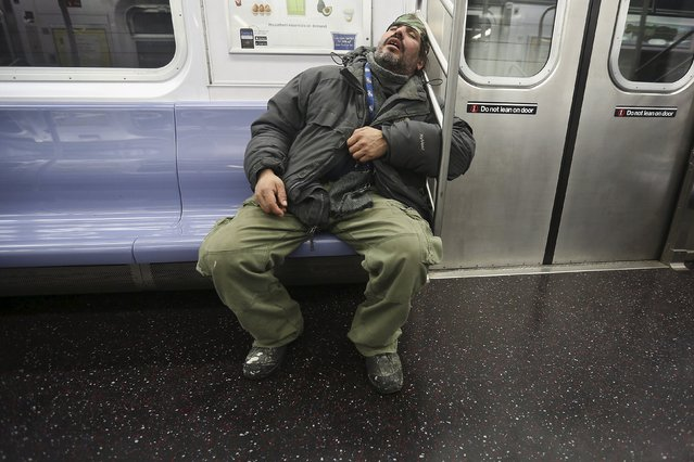 A man sleeps on the subway as it pulls into the 34th Street Hudson Yards station in the Manhattan borough of New York, January 6, 2016. (Photo by Carlo Allegri/Reuters)
