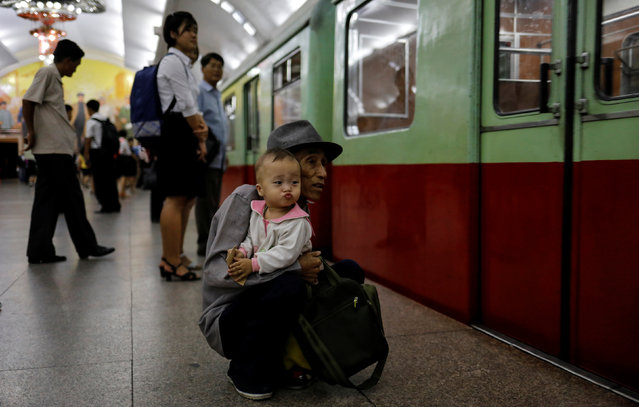 A man waits with his grandson as a train arrives at a subway station in Pyongyang, North Korea on September 11, 2018. (Photo by Danish Siddiqui/Reuters)