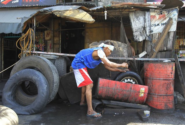 A worker submerges a tyre in a an old discarded oil barrel which is used as a water basin as he cleans it and checks for holes in front of his vulcanising shop in Manila February 10, 2015. (Photo by Romeo Ranoco/Reuters)