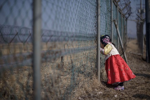 A girl wearing a traditional hanbok dress stands at a military fence facing towards North Korea at Imjingak park, south of the Military Demarcation Line and Demilitarized Zone (DMZ) separating North and South Korea, on February 19, 2015. South Korean families separated during the Korean war often visit the DMZ to offer prayers to their relatives in the North, on the occasion of the Lunar New Year. (Photo by Ed Jones/AFP Photo)