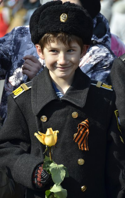 A member of a local youth club, which teaches military and patriotic classes, holds a flower during celebrations for the Defender of the Fatherland Day in the far eastern city of Vladivostok February 23, 2015. (Photo by Yuri Maltsev/Reuters)