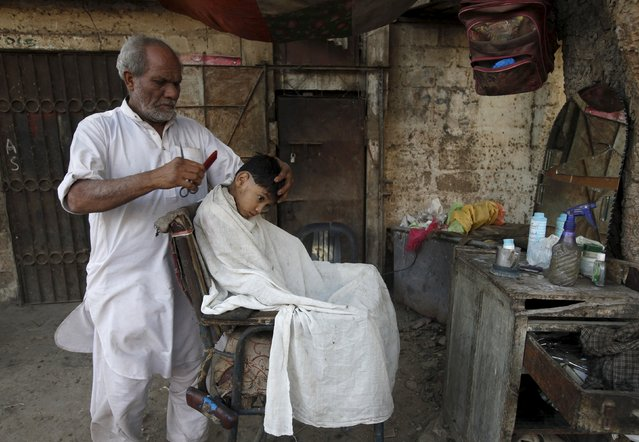 A boy in apron gets his hair cut at a makeshift barber stall along a street in a low income residential area in Karachi, Pakistan, December 27, 2015. (Photo by Akhtar Soomro/Reuters)