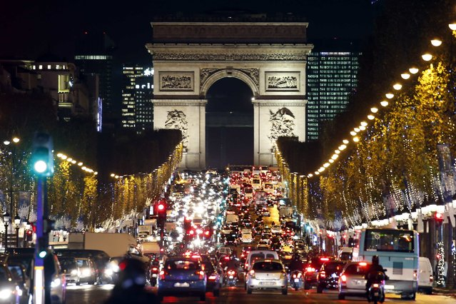Christmas holiday lights hang from trees to illuminate Champs Elysees avenue in Paris as rush hour traffic fills the avenue leading up to the Arc de Triomphe, France, November 19, 2015. (Photo by Charles Platiau/Reuters)