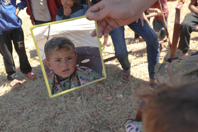 Syrian child looks his hairstyle in a hand mirror as volunteer barbers give free haircuts to children who escaped from the attacks of the Assad regime and settled in makeshift tents, ahead of the upcoming Eid al-Fitr in Idlib, Syria on May 12, 2021. (Photo by Izzettin Kasim/Anadolu Agency via Getty Images)