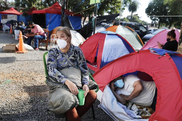 Relatives of COVID-19 patients camp outside the Ingavi Hospital in San Lorenzo, Paraguay, Wednesday, June 2, 2021. The relatives maintain a round-the-clock vigil to provide the food and medicines for their hospitalized family members. (Photo by Jorge Saenz/AP Photo)