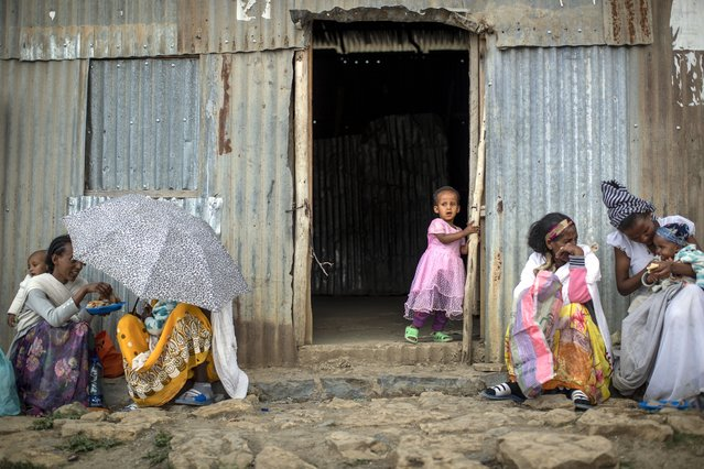 A Tigrayan girl looks out of a doorway as others sit next to a metal shack at a reception center for the internally-displaced in Mekele, in the Tigray region of northern Ethiopia, on Sunday, May 9, 2021. Despite claims by both Ethiopia and Eritrea that they were leaving, Eritrean soldiers are in fact more firmly entrenched than ever in Tigray, The Associated Press has found. (Photo by Ben Curtis/AP Photo)