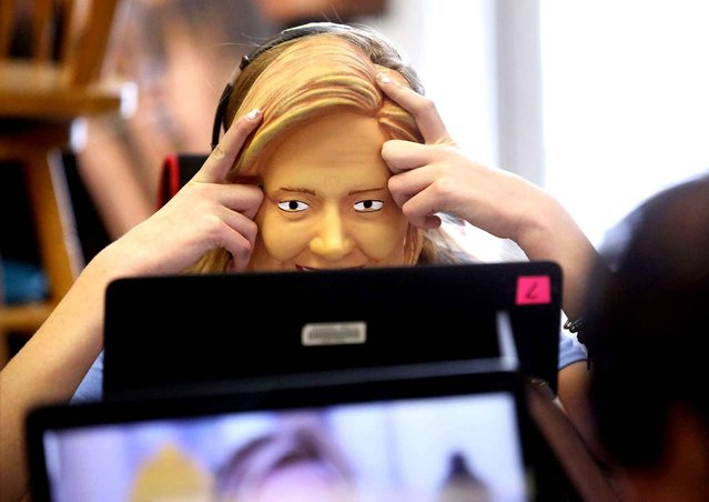 Eighth-grader Michelle Kemp, wearing a Hillary Clinton mask, watches presidential candidate videos Tuesday, January 26, 2016, during Iowa Youth Presidential Straw Poll at Eleanor Roosevelt Middle School in Dubuque, Iowa. (Photo by Jessica Reilly/Telegraph Herald via AP Photo)