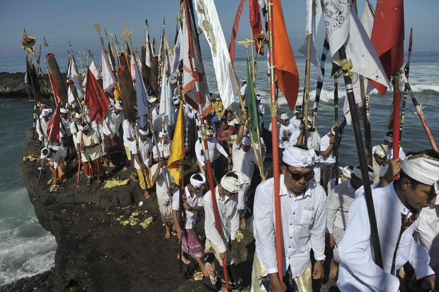 Balinese Hindus walk along the shore during the Melasti ceremony ahead of Nyepi day at Pererenan Beach on the Indonesian island of  Bali March 18, 2015 in this photo taken by Antara Foto. (Photo by Nyoman Budhiana/Reuters/Antara Foto)