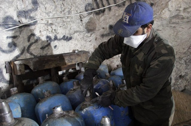 A man works on gas canisters filled with explosives inside a cave used as a weapon factory and operated by rebel fighters from Suqour al-Sham Brigade in Idlib countryside March 18, 2015. (Photo by Mohamad Bayoush/Reuters)