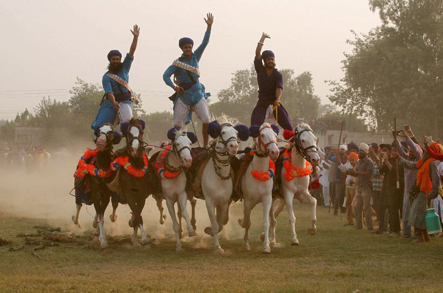 Nihangs or Sikh warriors, display their skills during a religious procession to mark the Bandi Chhor Divas in Amritsar, India, November 8, 2018. Sikhs celebrate Bandi Chhor Divas a day after Diwali to mark the return of their Sixth Guru, Guru Hargobind, who was freed from imprisonment from the fort of Gwalior by Mughal Emperor Jahangir in 1619. (Photo by Munish Sharma/Reuters)