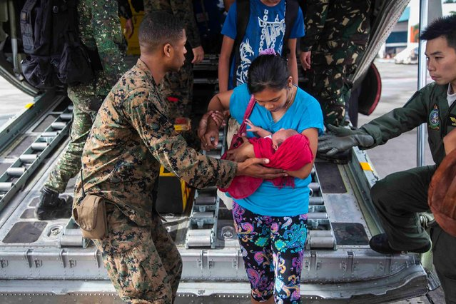 In this Tuesday, November 12, 2013, photo provided by the Navy Media Content Service (NMCS), U.S. Marine Lance Cpl. Xavier L. Cannon and members of the Philippine Armed Forces help civilians displaced by Typhoon Haiyan disembark a C-130 aircraft at Villamor Air Base., Philippines. U.S. service members are assisting the Armed Forces of the Philippines in the recovery efforts for the people affected in the aftermath of Typhoon Haiyan. (Photo by Lance Cpl. Anne K. Henry/AP Photo/NMCS/Released)