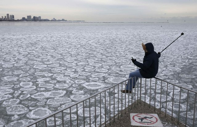 Charles Martinez sits on a railing to take a selfie overlooking the partially frozen Lake Michigan in Chicago, Illinois, in this January 5, 2015 file photo. (Photo by Jim Young/Reuters)