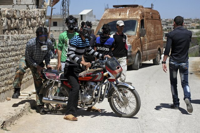 Civilians react as they wear gas masks after what activists said was a chlorine gas attack on Kansafra village at Idlib countryside, Syria May 7, 2015. (Photo by Abed Kontar/Reuters)