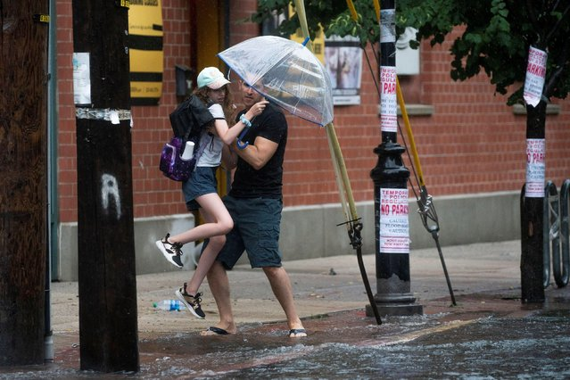 People make their way on a flooded street as Tropical Storm Elsa passes through Hoboken, New Jersey, U.S., July 9, 2021. (Photo by Eduardo Munoz/Reuters)