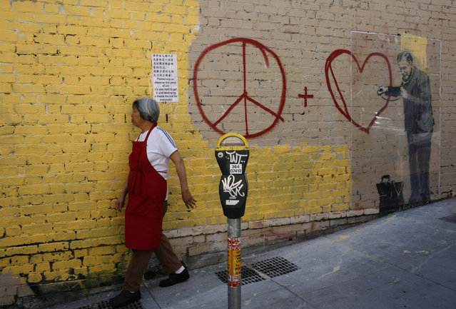 A woman walks past a painting, believed to be the work of elusive British street artist Banksy, in the Chinatown section of San Francisco, May 4, 2010. (Photo by Robert Galbraith/Reuters)