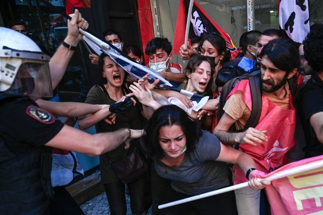 Protesters clash with police officers during a rally, in the Kadikoy district, in Istanbul, on July 20, 2021, called to mark on the anniversary of the 2015 suicide attack that took place in the southern Turkish town of Suruc. Leftist youth gathered to protest as they mark the anniversary of a suicide bomb attacks which killed 31 people in Suruc, where activists had gathered to prepare for an aid mission to the nearby Syrian town of Kobane. It was one of the deadliest attacks in Turkey in recent years, and, the first time the government has directly accused the Islamic State group of carrying out an act of terror on Turkish soil. (Photo by Bulent Kilic/AFP Photo)
