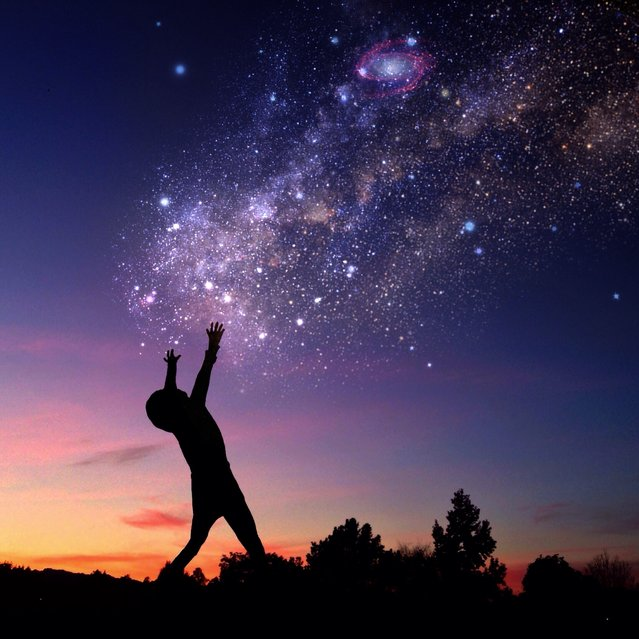 A boy holds his hands up to a starry night sky. (Photo by Ali Jardine/Caters News)