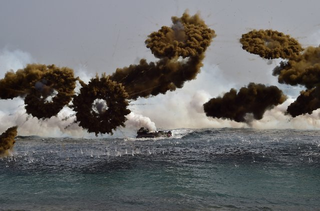South Korean Marine amphibious assault vehicles fire smoke shells to land on the seashore during a joint landing operation by US and South Korean Marines in the southeastern port of Pohang on March 30, 2015. The drill is part of the annual joint exercise Foal Eagle to enhance the combat readiness of the US and South Korea supporting forces in defense of the Korean Peninsula. (Photo by Jung Yeon-Je/AFP Photo)