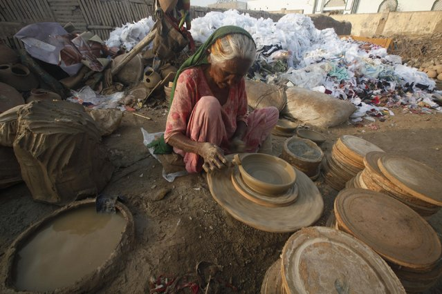 A potter works on a clay pot at a small traditional factory on the outskirts of Karachi February 19, 2015. (Photo by Athar Hussain/Reuters)