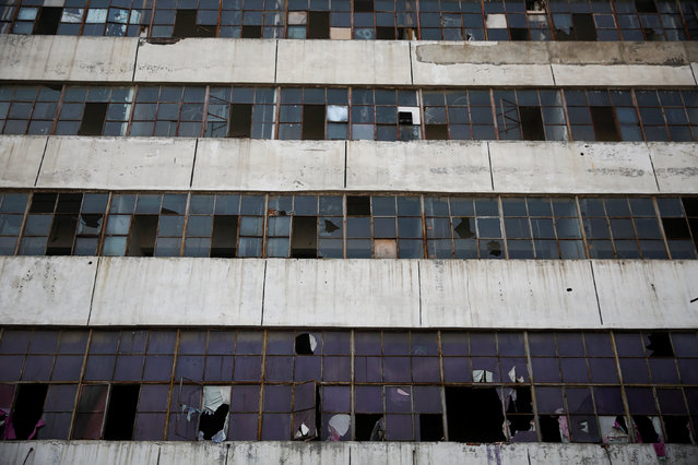 Broken windows of an abandoned factory complex overlook the set of the post-apocalyptic movie Zombie Era in Langfang, Hebei province, China December 16, 2016. (Photo by Damir Sagolj/Reuters)