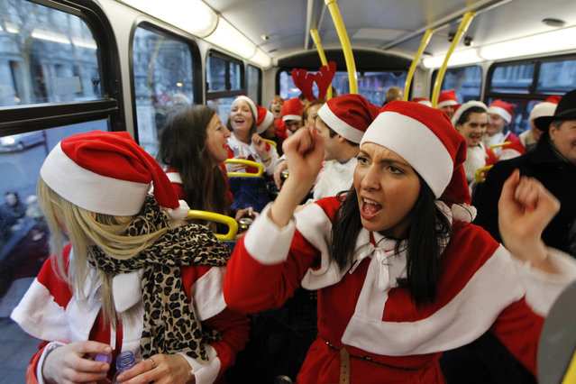 In this December 15, 2012 file photo, revellers dressed up in Santa outfits travel on a bus in London during a SantaCon festival parade through the streets of London. (Photo by Sang Tan/AP Photo)