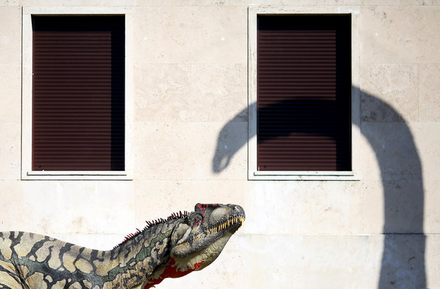 A scale model of a dinosaur and a shadow of another are seen displayed in front of La Sapienza University headquarter in Rome, April 10, 2015. (Photo by Alessandro Bianchi/Reuters)