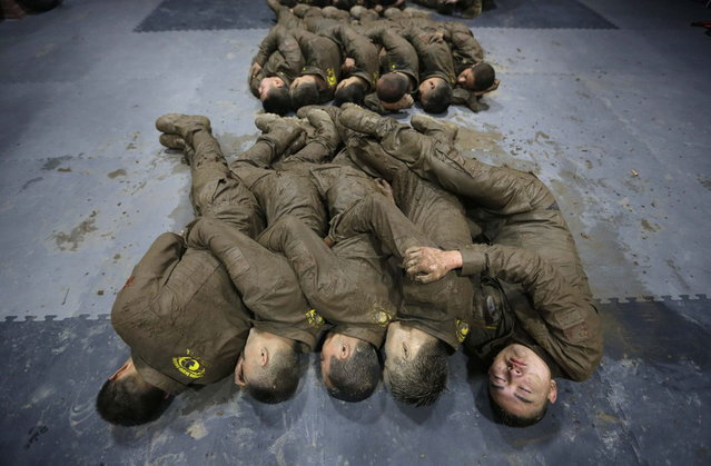 Students hold each other for warmth as they sleep during a break in between high intensity training at Tianjiao Special Guard/Security Consultant camp on the outskirts of Beijing December 1, 2013. (Photo by Jason Lee/Reuters)