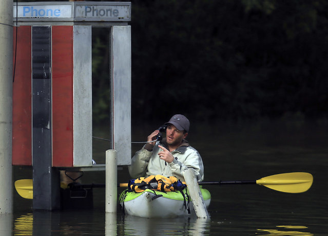 With Russian River waters rising, Dustin Coupe of Guerneville talks with an operator via phone booth on River Road in Guerneville, Calif., Wednesday. January 11, 2017. Dozens of Northern California residents have been rescued by boats and firetrucks from flooded homes near Hollister, California as a drought-busting series of storms moved out of the region. Days of rain and snow have toppled trees and forced people out of water-logged homes. (Photo by Kent Porter/The Press Democrat via AP Photo)