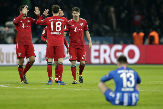 Hertha's Lukas Kluenter sits on the pitch as Bayern's players celebrate after a German Soccer Cup round of sixteen match between Hertha BSC Berlin and FC Bayern Munich in Berlin, Germany, Wednesday, February 6, 2019. Munich defeated Berlin by 3-2. (Photo by Michael Sohn/AP Photo)