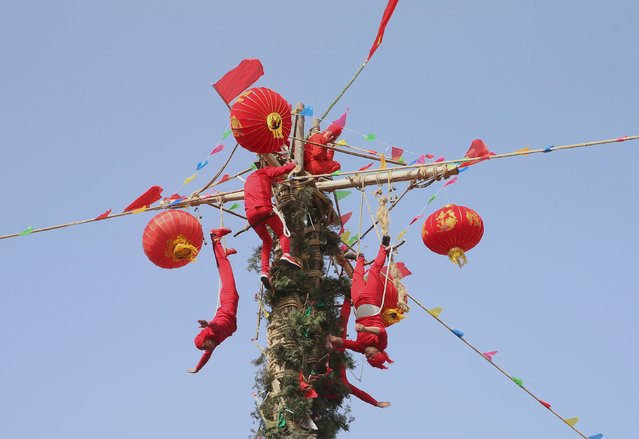 Folk artists perform a show as they climb up a ladder built with sticks and knives at a local folk art festival in Chengcheng, Shaanxi Province, China, February 19, 2016. (Photo by Reuters/Stringer)