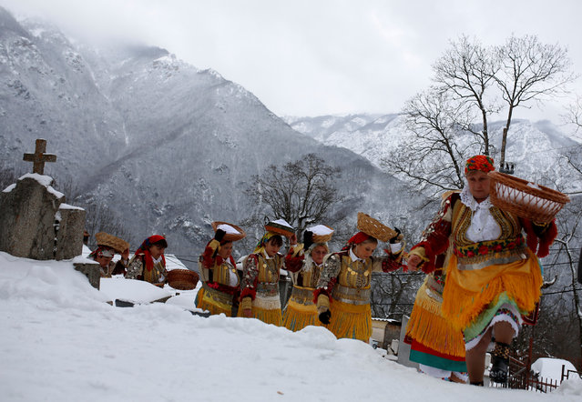 Women dressed in traditional folk costumes balance baskets of bread on their heads during an Epiphany day celebration in Bitushe village, Macedonia January 19, 2017. (Photo by Ognen Teofilovski/Reuters)