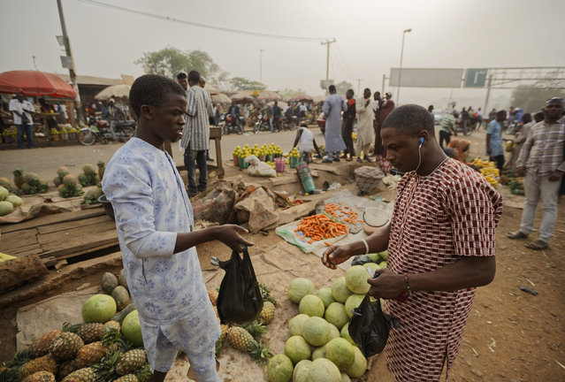 A customer, right, buys fruit from a street seller by the side of the road at a busy intersection near Nyanya, on the eastern outskirts of the capital Abuja, Nigeria Tuesday, February 12, 2019. (Photo by Ben Curtis/AP Photo)