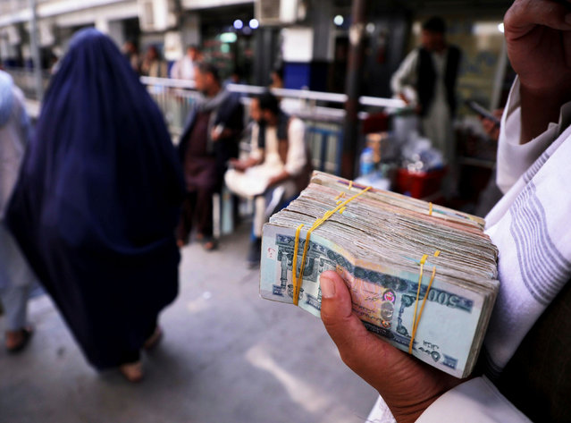 A man holds a bundle of Afghan banknotes at a money exchange following the reopening of banks and markets in Kabul, Afghanistan on September 4, 2021. (Photo by Reuters/Stringer)