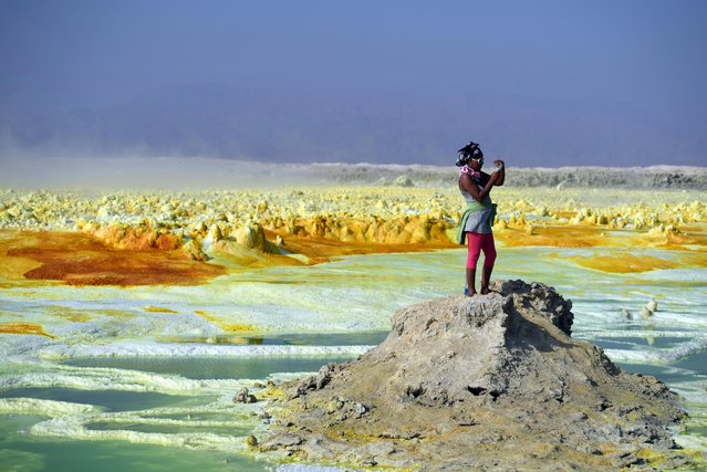 A tourist take a photograph of a sulphur lake in the Danakil Depression on January 23, 2017 near Dallol, Ethiopia. (Photo by Carl Court/Getty Images)