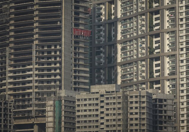 Windows of high-rise residential buildings which are under construction are seen surrounding a residential tower (R) in central Mumbai January 12, 2015. The cost for buying a 2400 square feet (223 square meters) three-bedroom apartment in the completed residential tower is around 36,400 Indian rupees ($ 580) per square feet or 87,360,000 Indian rupees ($1.40 million). (Photo by Danish Siddiqui/Reuters)