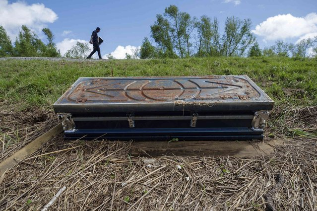 Jeremy Salvant walks on the Mississippi River levee to avoid snakes and passing the casket of John Chaney, after rescuing family photographs from his mold filled destroyed home in Ironton, La., Sunday, September 19, 2021, three weeks after the wind and storm surge from Hurricane Ida devastated the historic African American community in Plaquemines Parish. (Photo by David Grunfeld/The Times-Picayune/The New Orleans Advocate via AP Photo)