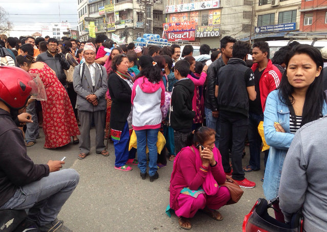 A group of people gather outdoors on a street as an earthquake hits Kathmandu city, Nepal, Saturday, April 25, 2015. (Photo by Niranjan Shrestha/AP Photo)