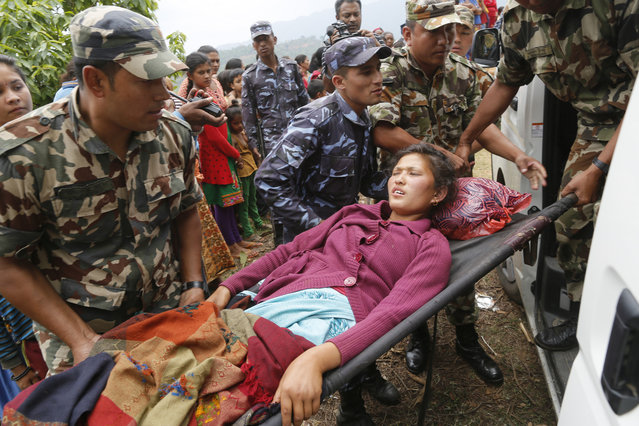 Sita Karka, suffering two broken legs from Saturday's massive earthquake, is assisted into an ambulance by Nepalese soldiers and police after arriving by helicopter from the heavily-damaged Ranachour village at a landing zone in the town of Gorkha, Nepal, Tuesday, April 28, 2015. (Photo by Wally Santana/AP Photo)