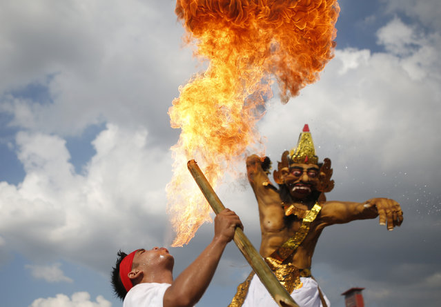 A Balinese Hindu blows fire, during a parade carrying Ogoh-ogoh effigies symbolising evil spirits, during a ritual before Nyepi, the day of silence, in Palembang, South Sumatra province, Indonesia March 8, 2016. Nyepi is a day of silence for self-reflection celebrating the Balinese Hindu new year, where people may not use lights, light fires, work, travel nor enjoy entertainment. (Photo by Darren Whiteside/Reuters)