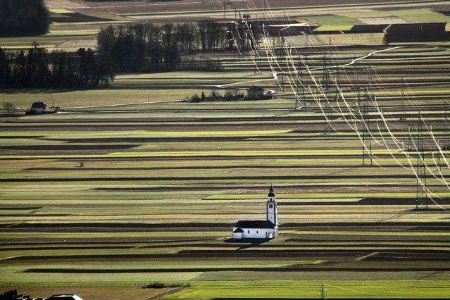 The church of Saint Ursula among green fields and power lines outside the village of Srednje Bitnje, Slovenia. (Photo by Eliane Haykal/The Guardian)