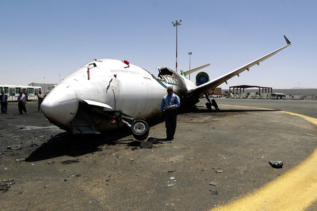 "A Yemeni airport official looks at a destroyed Felix Airways plane, after it was hit in an air strike, at the international airport of Yemen's capital, Sanaa, on April 29, 2015. Coalition warplanes destroyed the runway at Sanaa's rebel-held airport after an Iranian plane ""defied"" a blockade on Yemeni airspace, the spokesman for the Saudi-led alliance said. (Photo by Mohammed Huwais/AFP Photo)"