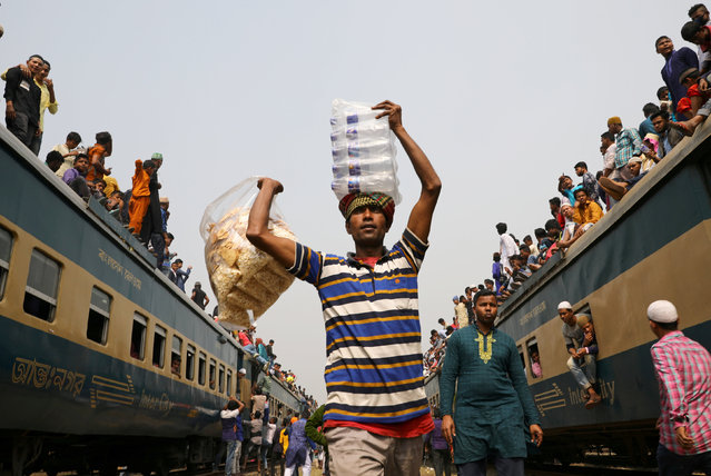 """A man sells water and dry food at a rail station during the final prayer meeting of """"Bishwa Ijtema"""", the world congregation of Muslims, on the banks of the Turag river in Tongi near Dhaka, Bangladesh, February 19, 2019. (Photo by Mohammad Ponir Hossain/Reuters)"""