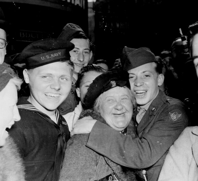 An American soldier hugs an English woman and as crowds celebrate Germany's unconditional surrender at Piccadilly Circus, in London, on May 7, 1945, in this handout photo provided by the United States National Archives. (Photo by Pfc. Melvin Weiss/Reuters/United States National Archives and Records Administration)