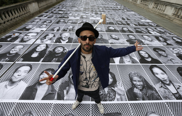 "JR poses with his public art installation ""Actions"" on the Terrace at Somerset House in London, England October 7, 2013. (Photo by Suzanne Plunkett/Reuters)"